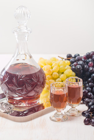 cristal: Cristal glasses and a carafe of liquor and grapes on the tray on white wooden background