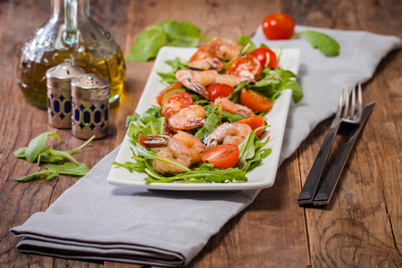 shrimp cocktail: Salad with shrimps or prawn, tomato and arugula on wooden background Stock Photo