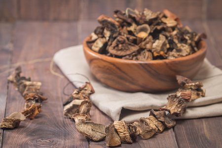 fungous: Dried mushrooms in wooden bowl on rustic background