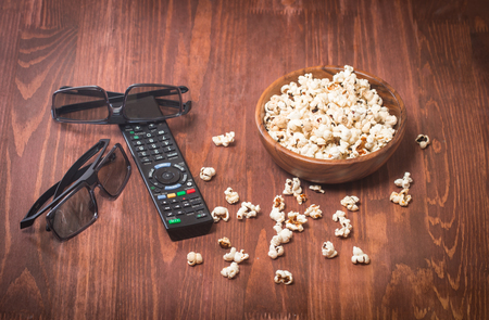 popcorn bowls: Popcorn, remote control and 3D glasses on wooden background Stock Photo