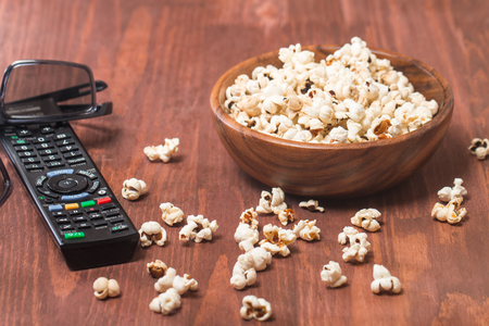 bowl of popcorn: Popcorn, remote control and 3D glasses on wooden background Stock Photo