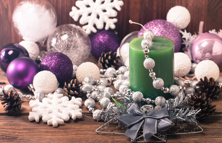 morado: Christmas Composition with Gifts and candle, white balls, pine cones, snowflakes on wooden table. Toned. Foto de archivo