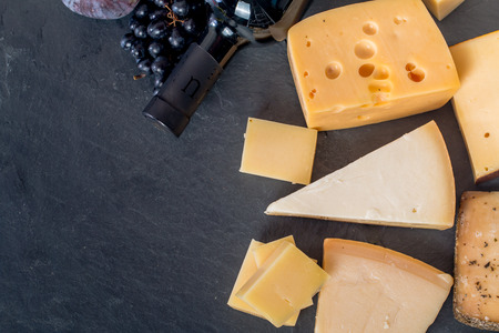 queso: Los diferentes tipos de quesos, el vino tinto, las uvas y figa a bordo negro, vista desde arriba Foto de archivo