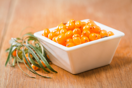 argousier: Sea-buckthorn berries in white bowl on a wooden background Banque d'images