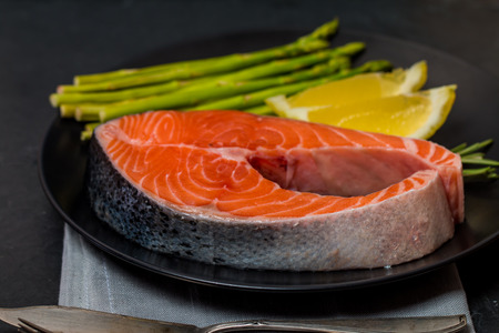 diet dinner: Delicious portion of fresh salmon steak with aromatic herbs, spices and vegetables on black background - healthy food, diet or cooking concept