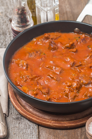 stew pan: Beef stew with tomato sauce in a pan on wooden background