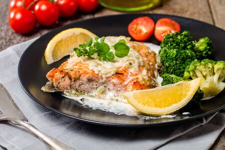steak tartare: Grilled Salmon Steak with Broccoli, Cream sauce and Lemon Wedges on wooden background