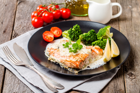 Grilled Salmon Steak with Broccoli, Cream sauce and Lemon Wedges on wooden background