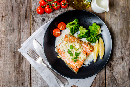 Grilled Salmon Steak with Broccoli, Cream sauce and Lemon Wedges on wooden background, top view.