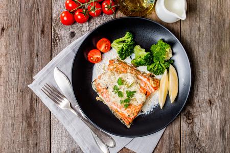 truchas: Filete de salmón con brócoli, salsa de crema y Cuñas de limón en el fondo de madera, vista desde arriba.
