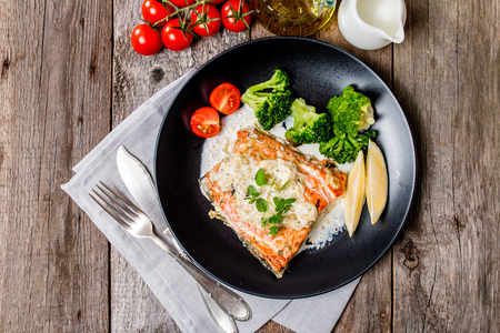 fish: Grilled Salmon Steak with Broccoli, Cream sauce and Lemon Wedges on wooden background, top view.