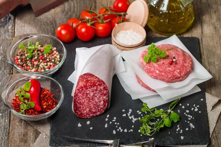 seasonings: Raw Ground meat Burger and salami with seasonings, tomato and olive oil on slate background