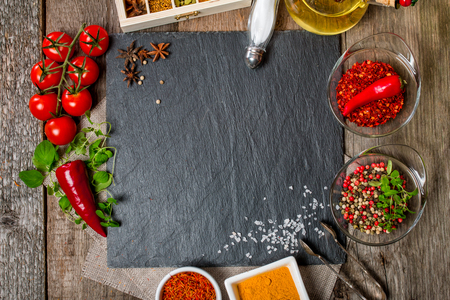 Alimentación de fondo, con espacio para texto, hierbas, especias, aceite de oliva, sal y verduras. Pizarra y la madera de fondo. Vista superior