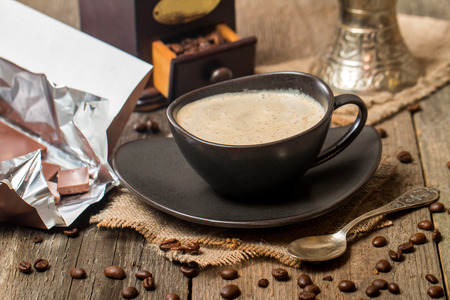 creamer: Cup of coffee with coffee beans and chocolate on wooden table