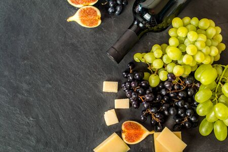 different types of cheese: Different types of grapess with bottle of wine, cheese and figs on black background. Top view. Stock Photo