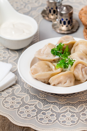 recipe decorated: Homemade Meat Dumplings - russian pelmeni with fresh parsley and sour cream on white plate Stock Photo