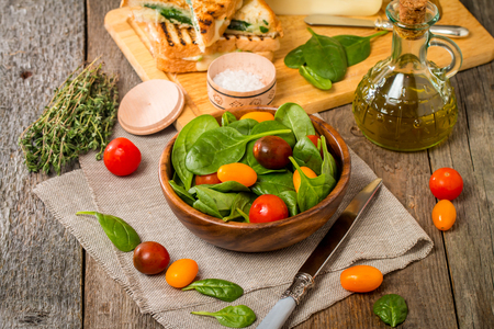 'baby spinach': Salad made with baby spinach and cherry tomatoes in a wooden bowl with ingredients. Stock Photo