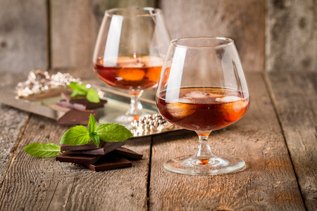 life: Vintage cognac still life with chocolate on wooden background