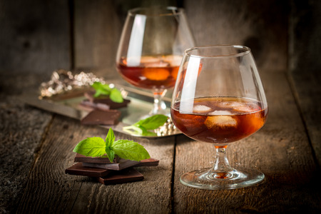 Vintage cognac still life with chocolate on wooden background