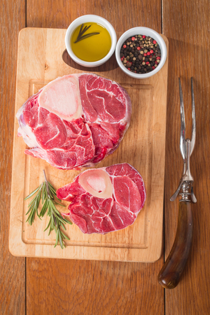 cross cut: Raw fresh cross cut veal shank and seasonings for making Osso Buco on wooden background