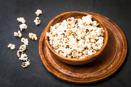 popcorn bowls: Closeup of popcorn in a bowl on black background