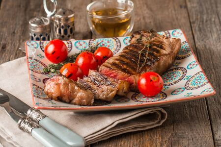 medium close up: Sliced medium rare grilled Beef steak Ribeye with grilled cherry tomatoes on plate on wooden background, close up