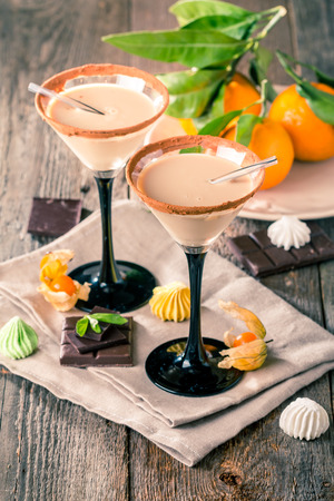 baileys: Irish cream liqueur in a glass with   cinnamon on wooden background