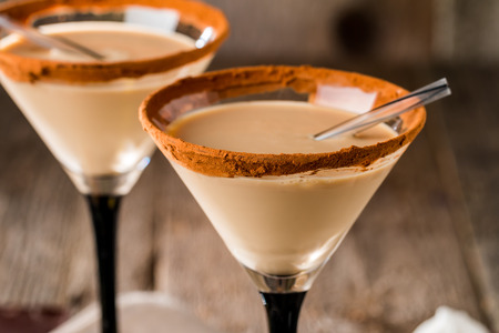 legless: Irish cream liqueur in a glass with   cinnamon on wooden background