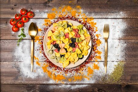 abstract food: colorful spices and farfalle on wooden table, top view