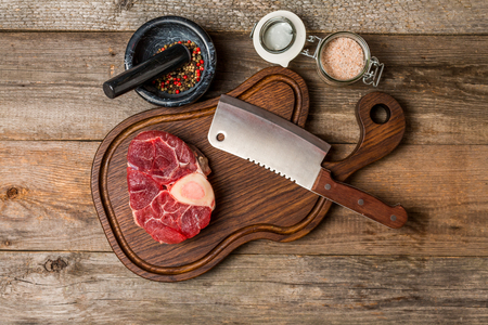 cross cut: Raw fresh cross cut veal shank and seasonings for making Osso Buco on wooden cutting board, top view Stock Photo