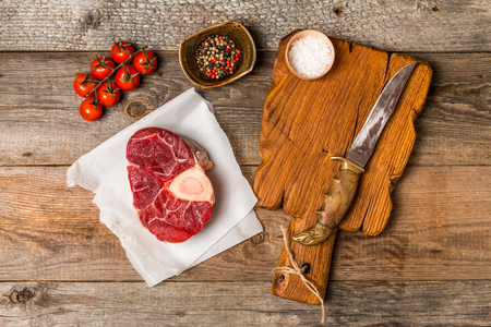 cross cut: Raw fresh cross cut veal shank and meat cleaver for making Osso Buco on wooden background, top view