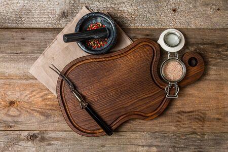 seasonings: Cutting board, seasonings and meat fork on  wooden background, top view