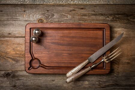 copy space: Chopping cutting board, seasonings and meat fork and knife carving set on wooden background, top view Stock Photo