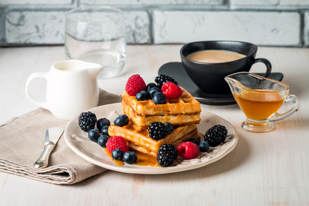 Fresh homemade brussels waffles with berries, chocolate and coffee for breakfast on white wooden background 스톡 콘텐츠