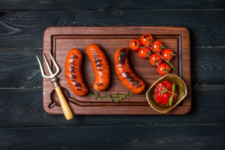 comida alemana: Grilled sausage with tomato and ketchup on wooden cutting board. top view