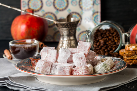 delight: Cup of coffee with turkish delight on oriental plate on black wooden background