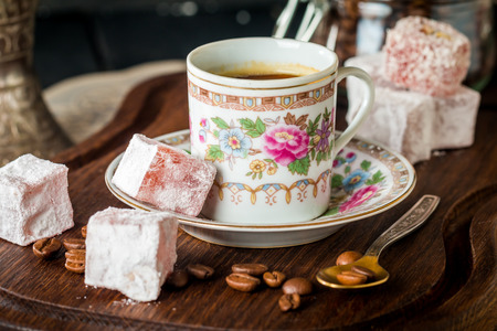 delight: Antique set of Turkish coffee with Turkish delight on black wooden table close-up
