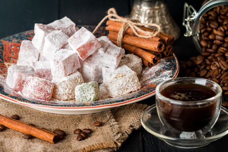 comida arabe: Cup of coffee with turkish delight on oriental plate on black wooden background
