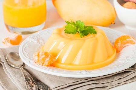 나무 테이블에 과일과 흰 접시에 망고 오렌지 푸딩