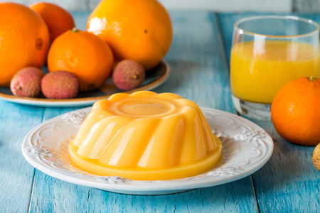 mango orange pudding on white plate with fruits on wooden table