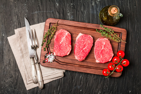 seasonings: Raw fresh Tender Steak  and seasonings on dark wooden background, top view Stock Photo