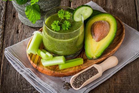 Sano jugo de jugo verde rodeado de aguacate, pepino, apio y chia semillas sobre fondo de madera Foto de archivo - 51242725