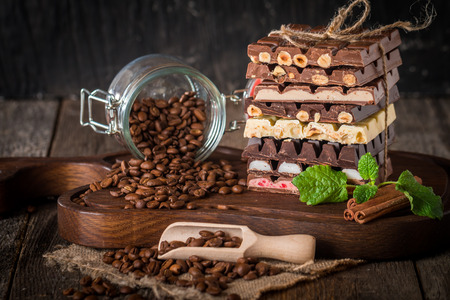 with fillings: An assortment of white, dark, and milk chocolate with nuts and with various fillings on wooden background