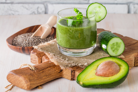 Healthy green juice smoothie surrounded by avocado, cucumber,  celery and chia seeds on white background Stok Fotoğraf
