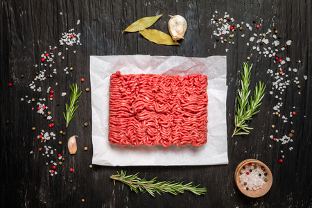 Minced meat on paper with seasoning and fresh rosemary on black background, top view