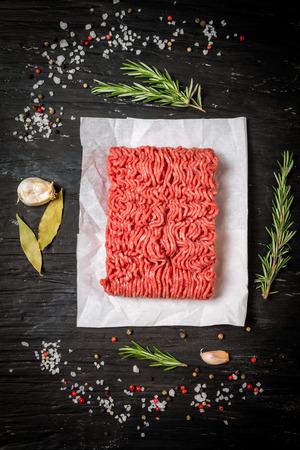 Carne tritata su carta con condimento e rosmarino fresco su sfondo nero, vista dall'alto