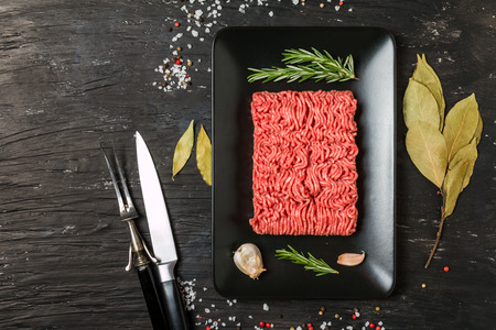 farce: Minced meat on black plate with seasoning and fresh rosemary on black background, top view