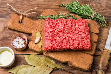 farce: Minced meat on cutting board with seasoning and fresh rosemary on wooden background, top view