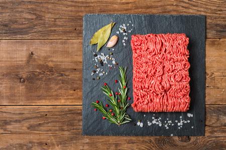 Carne tritata su una tavola di pietra nera ardesia con condimenti e rosmarino fresco su fondo in legno, vista dall'alto Archivio Fotografico