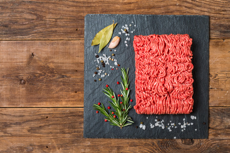 farce: Minced meat on a slate stone black board with seasonings and fresh rosemary on wooden background, top view